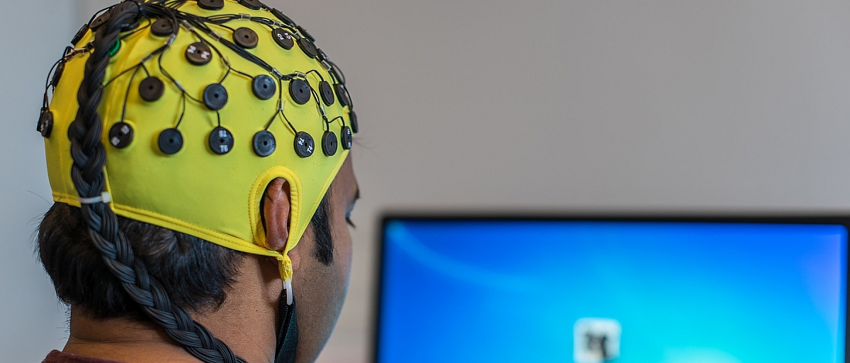 Man facing a computer screen with yellow skullcap on with black electrodes all over it and a braid of black wires snaking out of the top down the back.